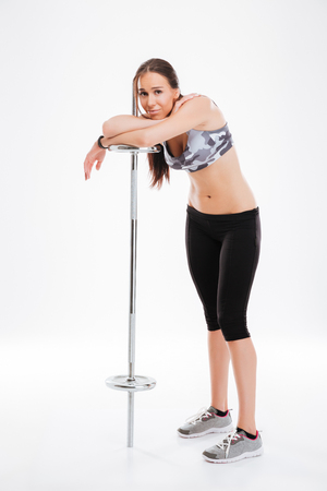 Full length pretty fitness girl with barbell. isolated white background
