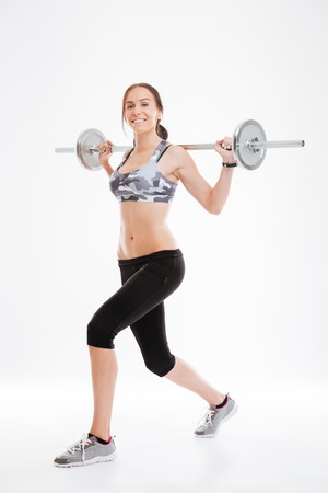 Full length fitness woman with barbell in studio. side view. isolated white background Stock Photo