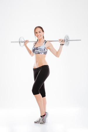 Full length fitness girl with barbell. looking at camera. isolated white background Stock Photo