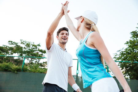 Happy young tennis players. Give me five Stock Photo