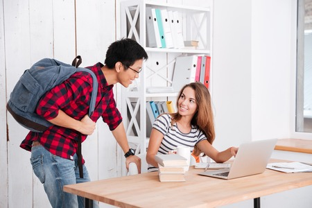18's: Cheerful female student pointing on display of laptop to her groupmate. Boy standing near girl and holding bag while looking on laptop and smiling. Stock Photo