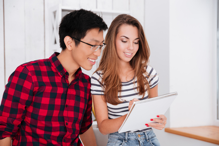 strip shirt: Picture of beautiful lady dressed in t-shirt in strip print and jeans writing in notebook and her groupmate wearing glasses looking at her notes.