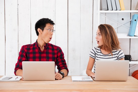 18's: Picture of two young students who were shocked from what was seen in the laptops in classroom. Looking at each other.