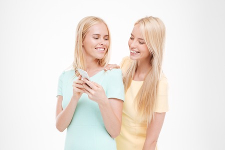 Picture of young cheerful lady showing her phone to the friend. Isolated over white background. Stock Photo