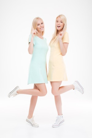 Picture of two attractive girls posing in the studio. Isolated over white background. Stock Photo
