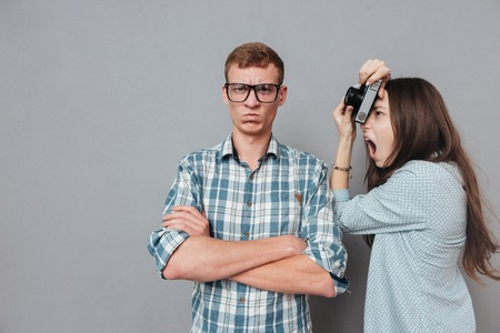 Annoyed hipster man in eyeglasses standing with arms folded while being photographed by a woman isolated on the gray background Stock Photo