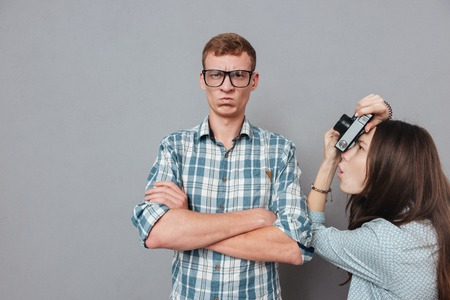 Angry hipster man in eyeglasses standing with arms folded while being photographed by a woman isolated on the gray background