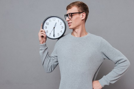 botanist: Botanist in glasses with clock. holding clock on shoulder. isolated gray background