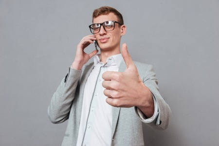 finger up: Hipster with phone showing finger up. isolated gray background Stock Photo