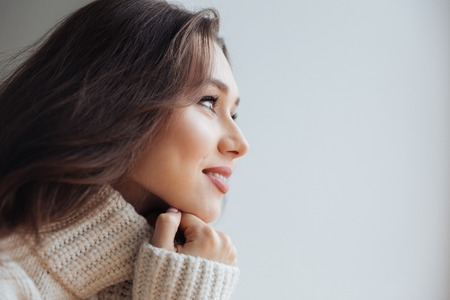 Side view of pretty model in sweater near the window. close up portrait Stock Photo