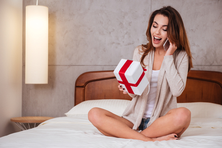 technolgy: Young excited woman holding gift box and talking on mobile phone while sitting on bed Stock Photo