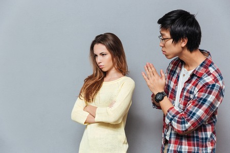 Young asian man asking for forgiveness his upset girlfriend isolated on the gray background Stock Photo
