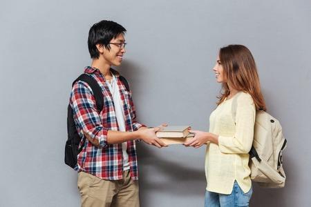 회색 배경에 고립 된 책을 교환 배낭 웃는 간의 학생 부부의 초상화 스톡 콘텐츠