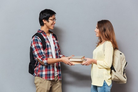 Portrait of a smiling interracial student couple with backpacks exchanging books isolated on the gray background