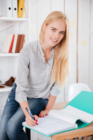 Portrait of a beaautiful young business woman sitting on a desk and making notes in documents
