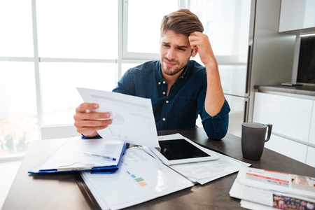 account executive: Young confused man analyzing finances at home while holding head with hand and looking at documents. Sitting near table with tablet.