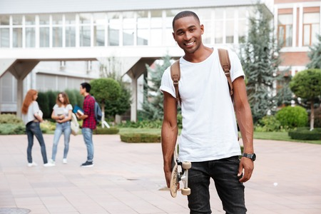 adult learners: estudiante alegre del afroamericano joven con mochila de pie y con el patín al aire libre