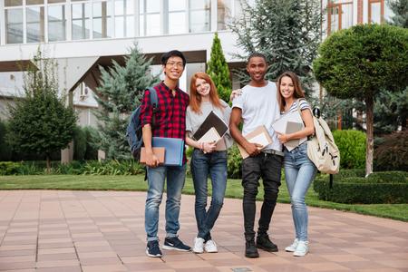 キャンパスで一緒に屋外で立って幸せな若い人の民族グループ