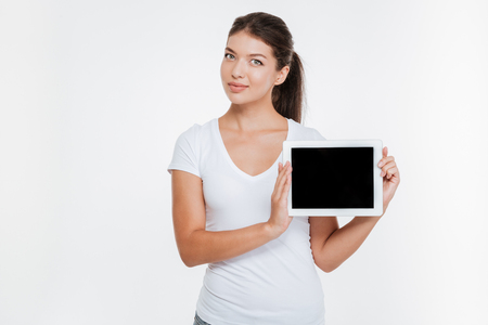 Image of young cheerful woman holding digital tablet and showing the display to camera. Isolated on white background. Stock Photo