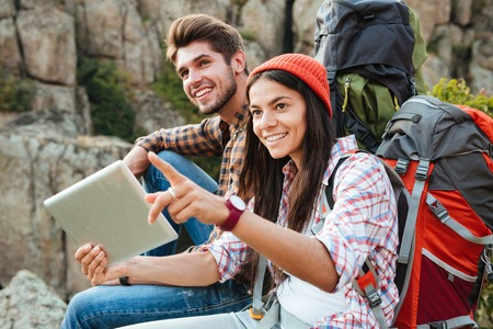 Young adventure couple with tablet near the canyon