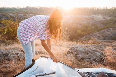 recoger: La muchacha recoge tienda de campaña en la montaña