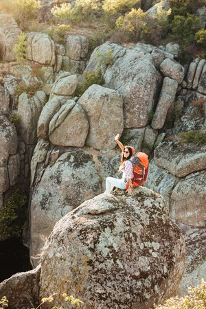 vetical: Vertical image of adventure woman on the rock. near the canyon