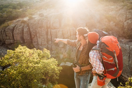 Adventure couple stands sideways near the canyon. man shows away Stock Photo