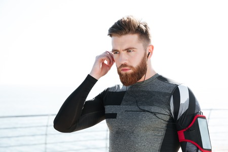 Handsome runner in headphones near the sea. side view Stock Photo