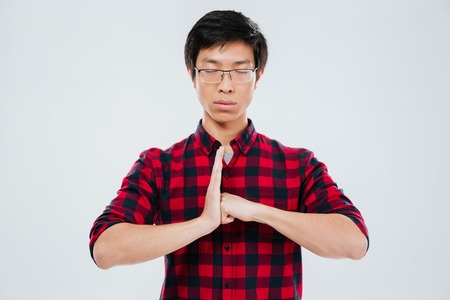 Photo of serious young man dressed in casual shirt in a cage and wearing eyeglasses make gesture with fist in palm. Isolated over white background.