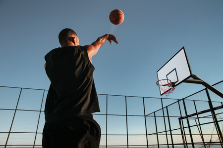 outdoor basketball court: Portrait of a basketball player taking a jump shot on an outdoor basketball court