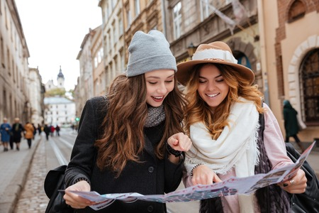 Two models outdoor. looking at map. in coat. warm clothes. so pretty girls. with hats