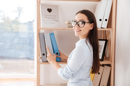 Cheerful young businesswoman taking folder from a book shelf while standing in office Stock Photo