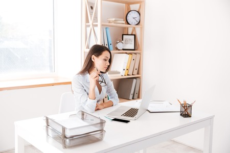 Concentrated businesswoman dressed in white shirt sitting in her office and looking at laptop while holding eyeglasses.