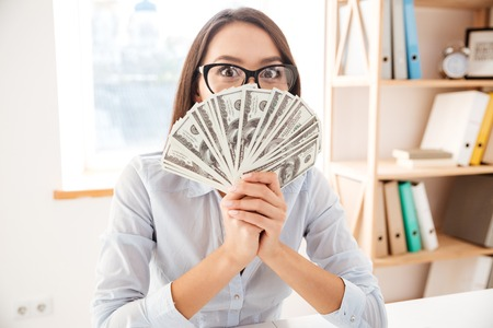 Picture of businesswoman dressed in white shirt sitting in her office and holding money in hand near face Stock Photo