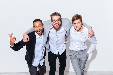 grupo de hombres: Tres hombres jóvenes alegres de pie y sonriente juntos sobre el fondo blanco