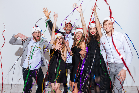 Group of cheerful excited young people in santa claus hats celebrating new year over white background 版權商用圖片