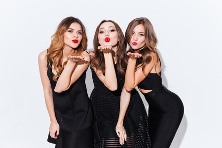 Three playful attractive young women standing and sending kisses over white background
