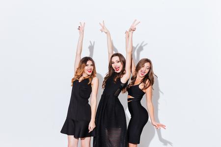 Drie gelukkige opgewonden jonge vrouwen dansen met opgeheven handen en het tonen van de vrede tekenen over een witte achtergrond Stockfoto