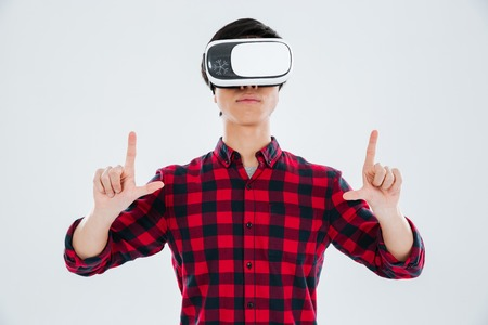 astonishing: Photo of young asian man dressed in casual shirt in a cage and wearing virtual reality device and holding an imagine copyspace. Isolated over white background.