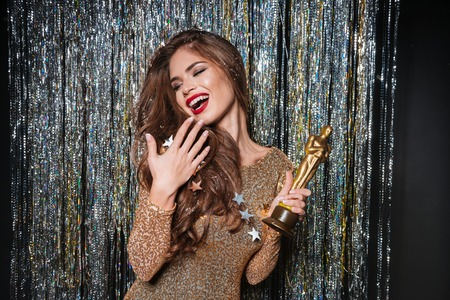 Happy young woman in evening dress laughing and holding award over sparkling background Stock Photo