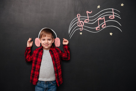 musically: Picture of little kid listening to music over black chalk board with musically drawings Stock Photo