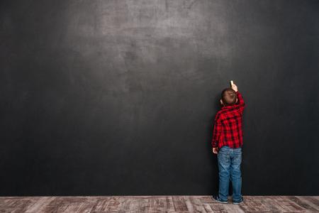 黒板の近くに立って、それを描く小さな子の写真。 写真素材