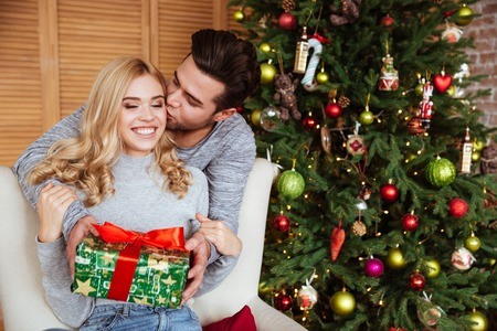 Young couple in sweaters with gift near the fir-tree. girl sitting on chair. man kissing girl
