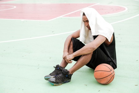 Photo of young tired african basketball player sitting in the park with towel.