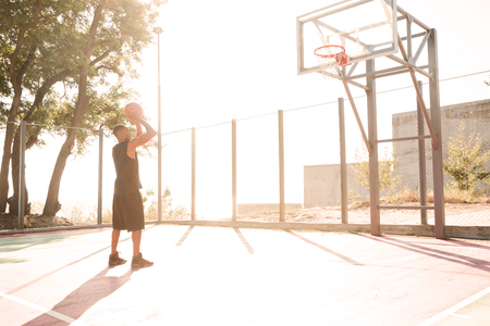 Picture of african basketball player practicing in the street with basketball hoop. Looking at hoop.