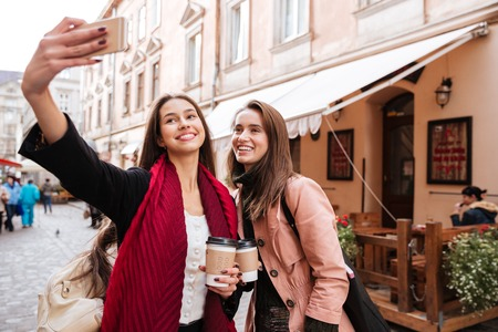 Two smiling beautiful young women taking selfie with mobile phone in old city