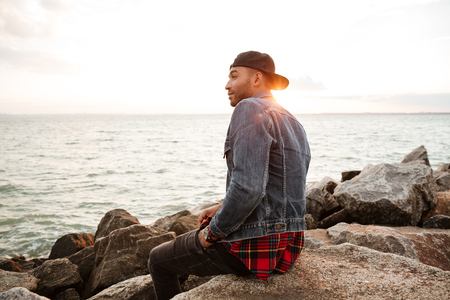 shiver: Image of african young man wearing cap walking on the beach. Looking aside. Stock Photo