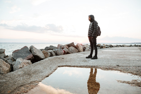 shiver: Photo of african young man dressed in warm clothes walking on the beach. Looking aside.
