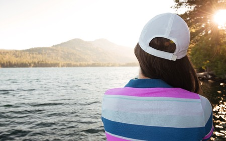 Back view portrait of a young woman looking at sunset on a lake