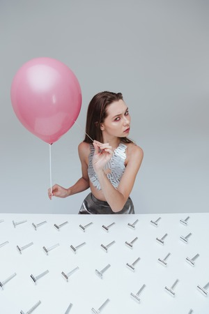 popped: Pretty young woman piercing pink balloon with needle at the table with old razor blades over white background Stock Photo